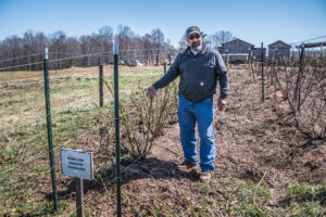 A man stands next to fences on his farm.