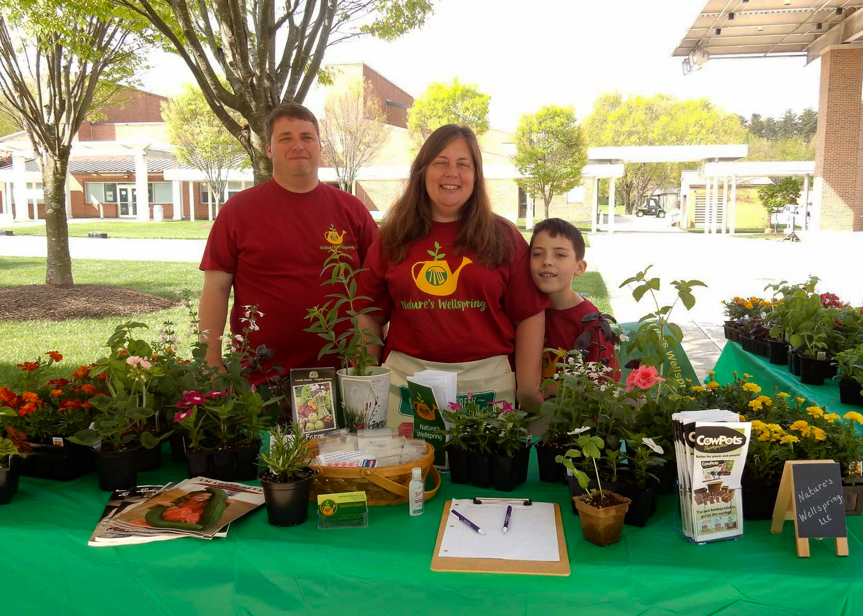 A Family Stands At A Farmer's Market Booth.