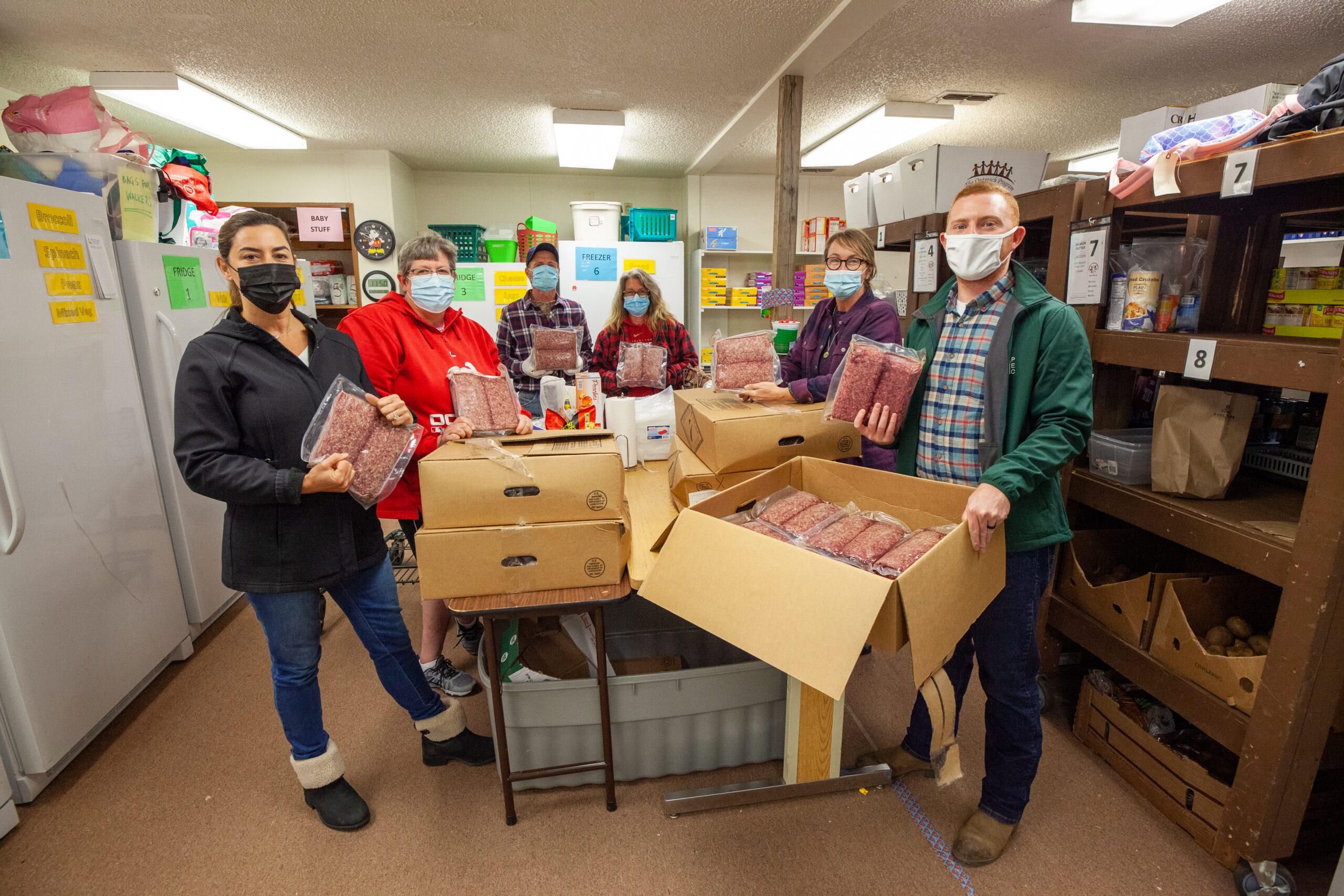 Volunteers Hold Packages Of Donated Beef At A Table.